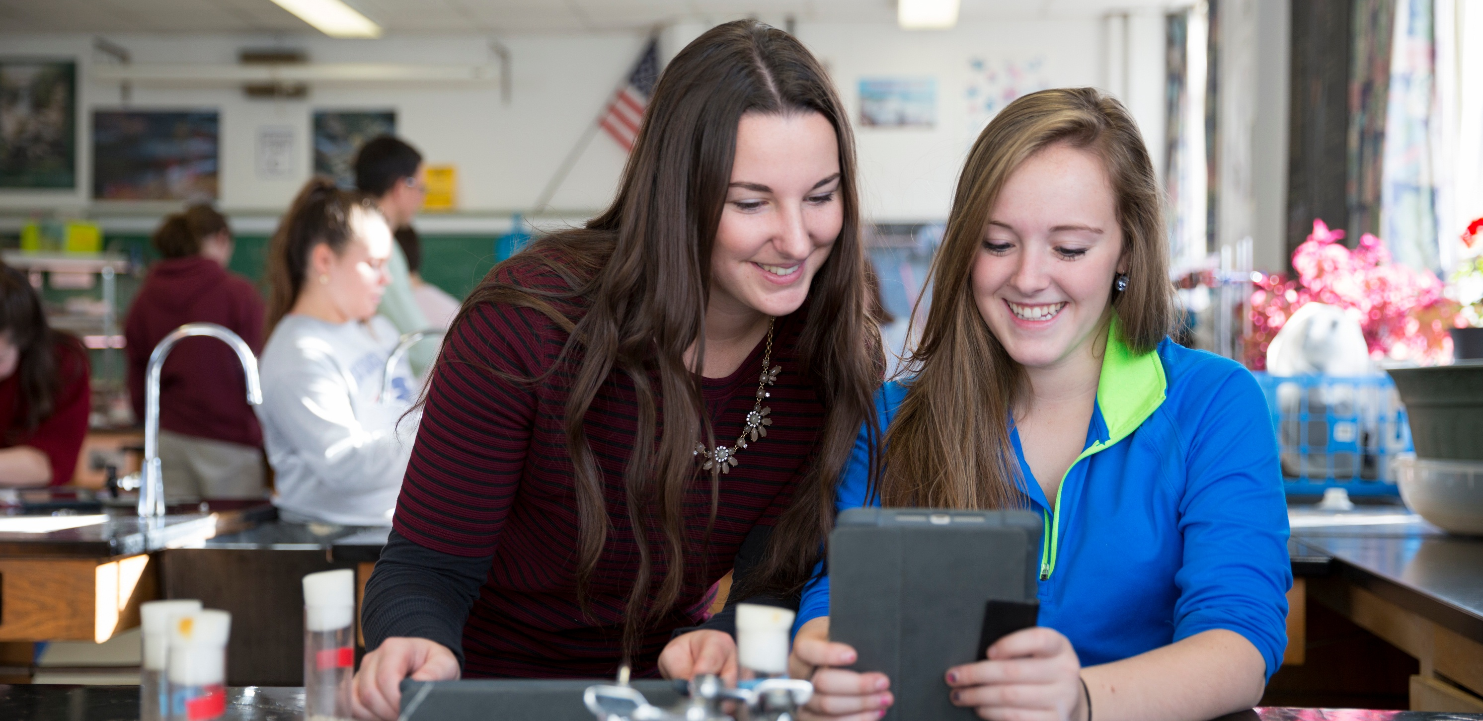 Two students use an iPad in the Chemistry lab.