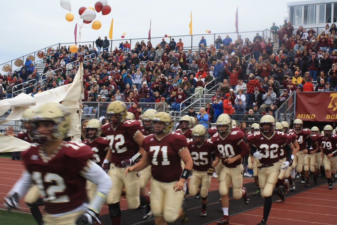 The football team rushes the field.
